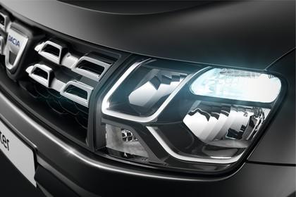 Dacia Duster SD Aussenansicht Front schräg statisch Studio Detail Grill und Scheinwerfer links grau